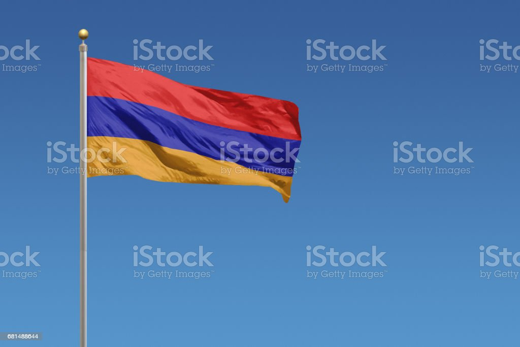 National flag of Armenia in front of a clear blue sky стоковое фото