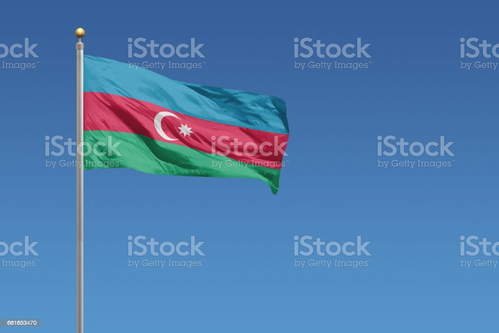 National flag of Azerbaijan on clear blue sky stock photo