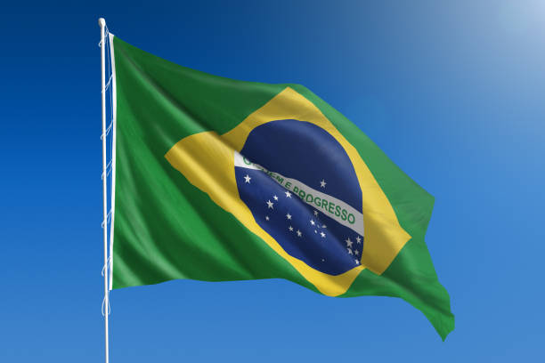 National flag of Brazil on clear blue sky stock photo