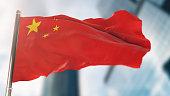 National Flag of China Against Defocused City Buildings