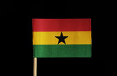 A national flag of Ghana on toothpick on black background. A horizontal triband of red, gold and green with a black star in centre