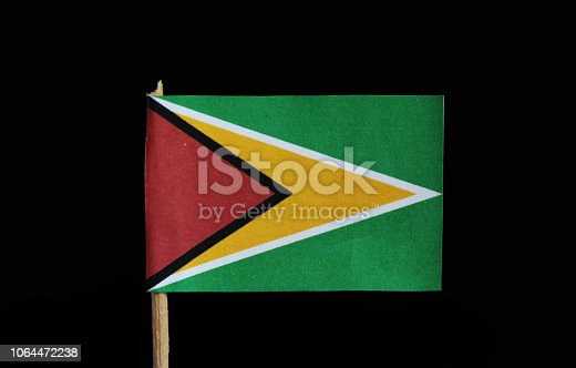 istock A national flag of Guyana on toothpick on black background. A green field with the black edged red isosceles triangle based on the hoist side superimposed on the larger white golden triangle. 1064472238