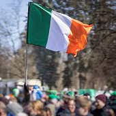 National Flag of Ireland close-up in hand on background of crowd people during the celebration of St. Patrick's Day in park, traditional carnival