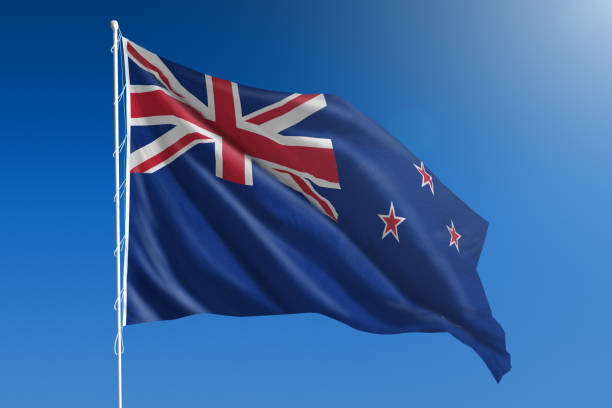national flag of new zealand on clear blue sky - new zealand flag stock photos and pictures
