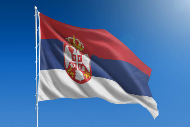 national flag of serbia on clear blue sky - serbia stock photos and pictures