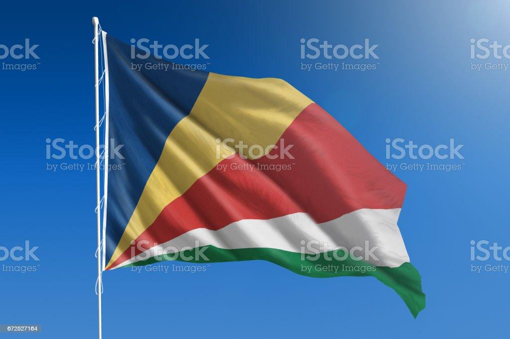 National flag of Seychelles on clear blue sky stock photo