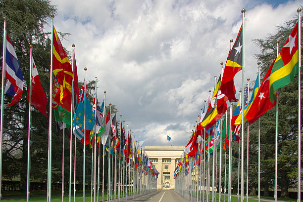 National flags gallery at the entrance to UN perspective view on an avenue with many national flags at the entrance to the UN, Geneva, Switzerland, under stormy clouds. diplomacy stock pictures, royalty-free photos & images