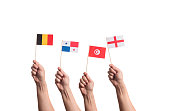 Little paper national flags in hands isolated on white background. Belgium, Panama, Tunisia, England.