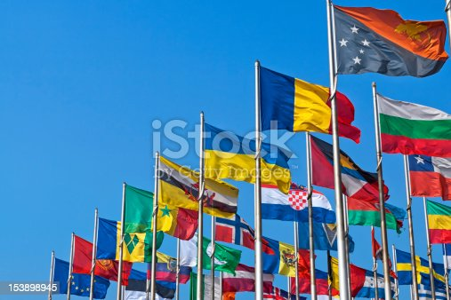 Different countries flags united together against blue sky