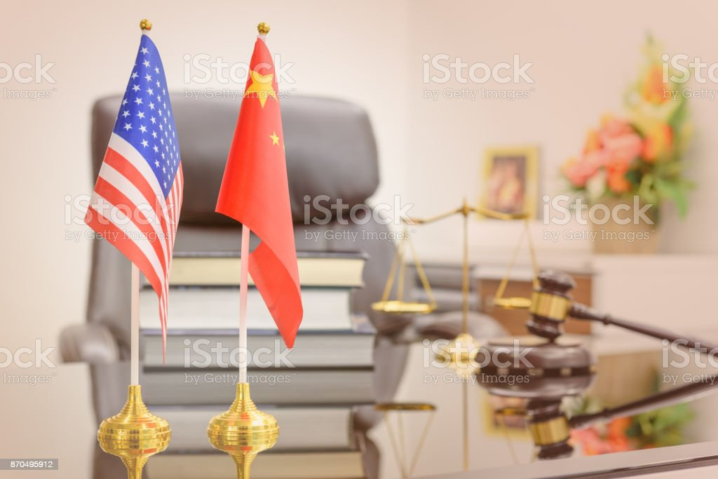 National flags of USA and China put on a table with books, gavel and a balance scale of justice behind. A symbol of cooperation between two nations, Washington and Beijing i.e. business dialogue, etc. stock photo