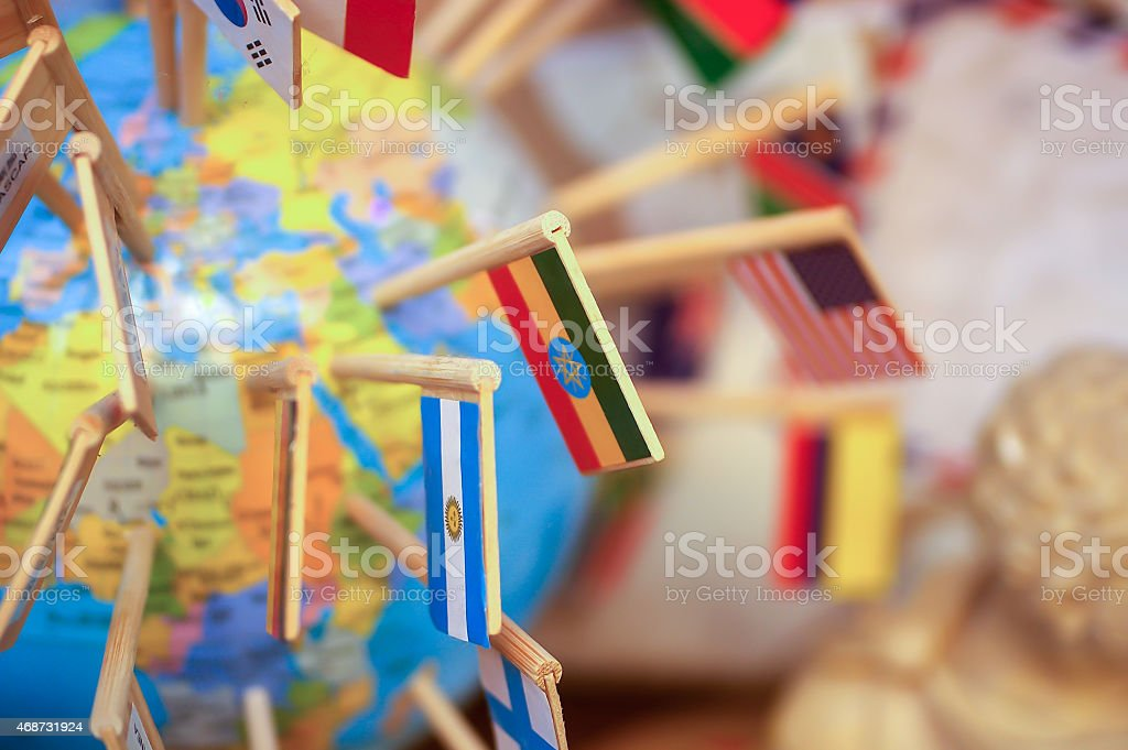 national flags stuck in the globe stock photo