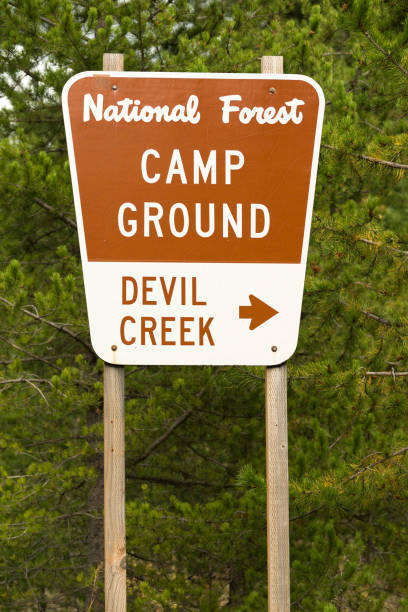 National Forest Sign Devil Creek Campground A metal sign along the highway points the way to Devil Creek Campground national forest stock pictures, royalty-free photos & images