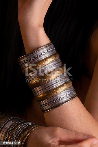 Wide gold bracelet on the girl's hands.