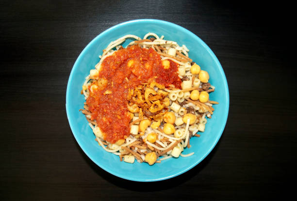 National Kushari in a turquoise plate on dark wooden background. Flat lay, top view. stock photo