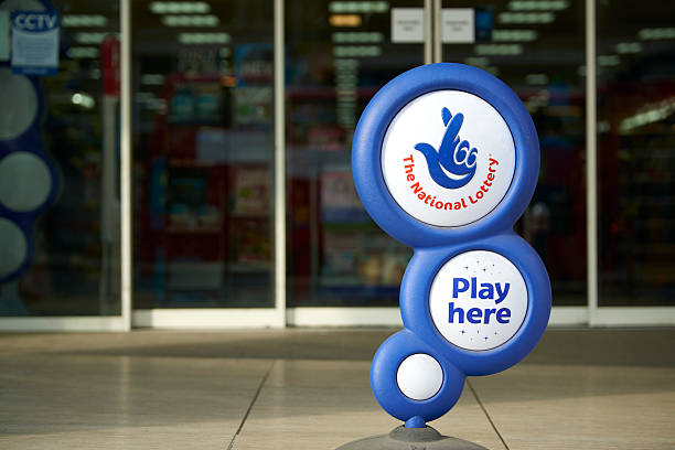 National Lottery sign London, UK - April 7, 2015: Blue National Lottery sign, showing its crossed fingers logo, in front of shop entrance. lottery stock pictures, royalty-free photos & images