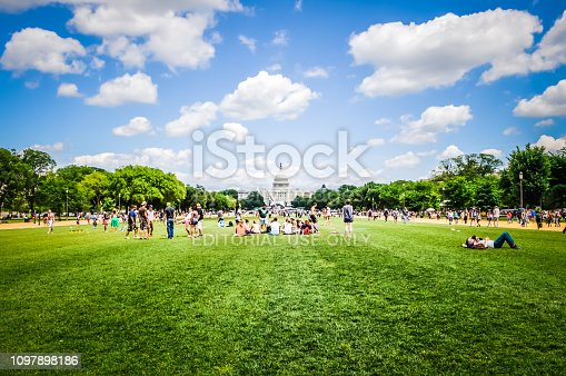 Washington, DC / USA - May 23 2014: View of the United States Capitol from National Mall. People are sitting on the grass in spring / summer in front of the Capitol Building in Washington DC