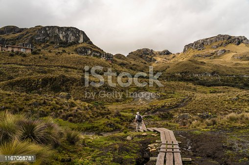 Distant men walking on boardwalk in the landscape of National park Las Cajas Mountains in Ecuador close to Cuenca city on 3850 altitude.