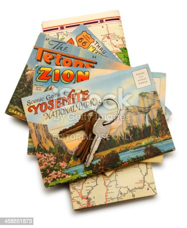 San Diego, California, USA - November 14, 2013: An old set of car keys on an old road map and a stack of postcards depicting Yosemite, Zion, and the Grand Teton National Parks. Shot in a studio setting on a white background.