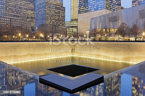 New York City, USA - February 1, 2018: Night time view of Manhattan skyscrapers and the reflecting pools of National September 11 Memorial commemorating the 9/11 attacks and the 1993 World Trade Center bombing. It is located at ground zero where the former World Trade Center twin towers originally stood.