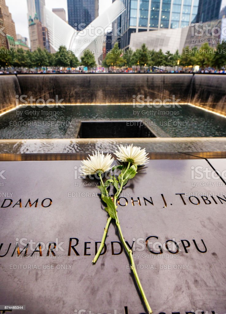 National September 11 memorial waterfalls with flowers and names stock photo