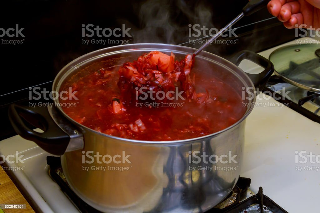 National Ukrainian borsch with sour cream and dill into the plate closeup stock photo