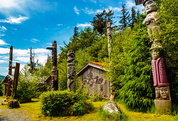 Native American Clan House and Totems Ketchikan, AK, USA - May 24, 2016:  Ketchikan, AK, USA - May 24, 2016:  Native American Totems and Clan Houses located at Totem Bight State Historic Site. ketchikan stock pictures, royalty-free photos & images