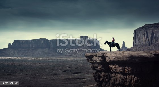 Subject: A native American Indian cowboy riding on a horse over a cliff looking into the stormy distance.