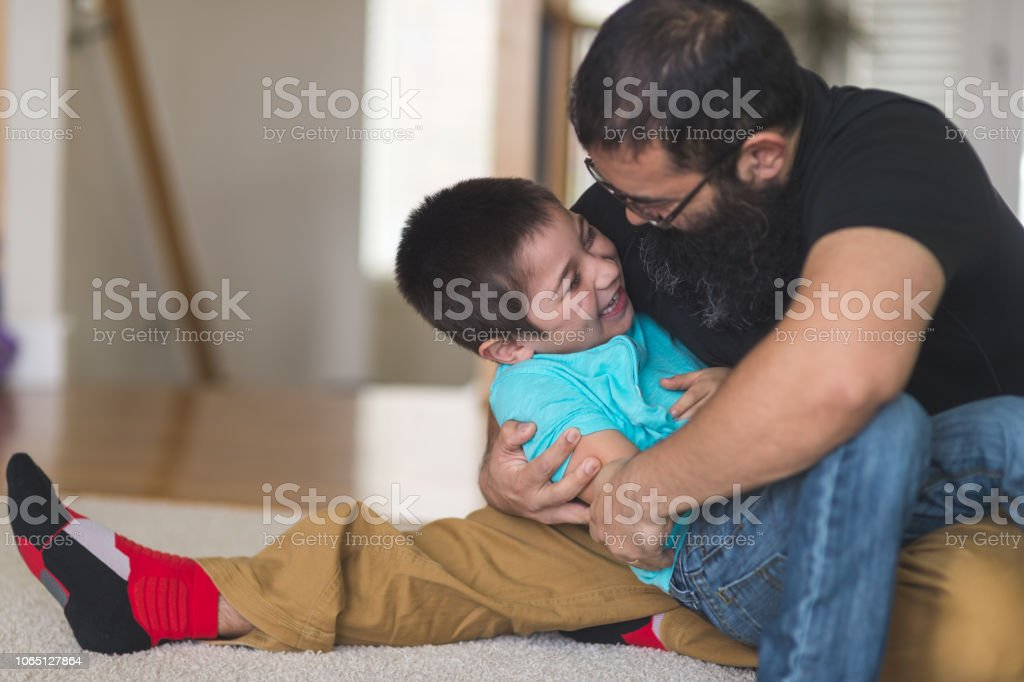 Native American Dad And Son Wrestling In The Living Room