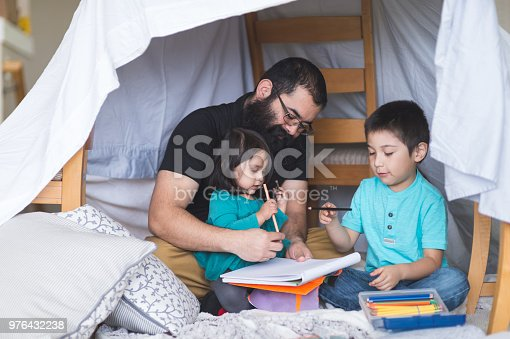 A Native American father draws with his two children under a makeshift fort made out of chairs and blankets. They're using colored pencils. Dad has a giant, burly beard.