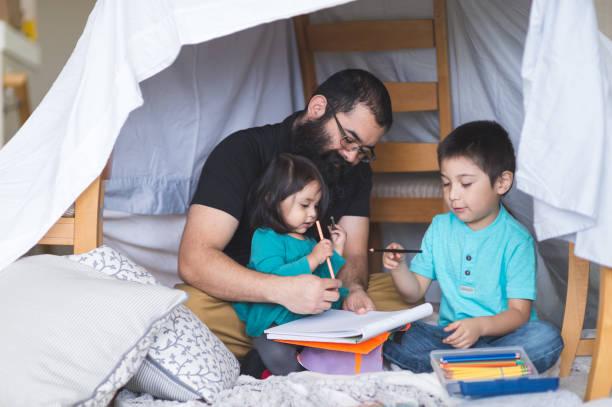 native american dad gör konst med sin unga barn under en provisorisk fort i vardagsrummet - fort bildbanksfoton och bilder