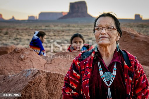 Beautiful proud portrait of a traditional Navajo grandmother with her grandson and granddaughter in front of the famous rock formations of the Monument Valley Tribal Park in Northern Arizona