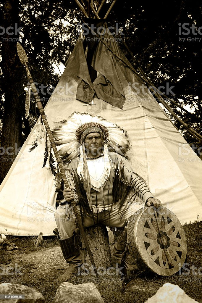 Native American in Traditional Dress Sitting Outside Teepee stock photo