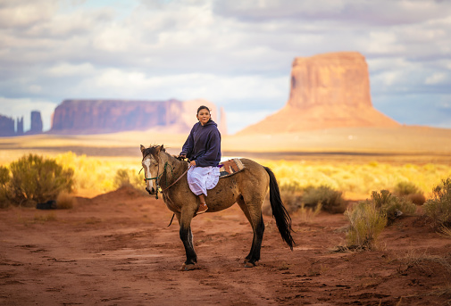 Native american indian riding horse on Navajo Nation's Monument Valley Park