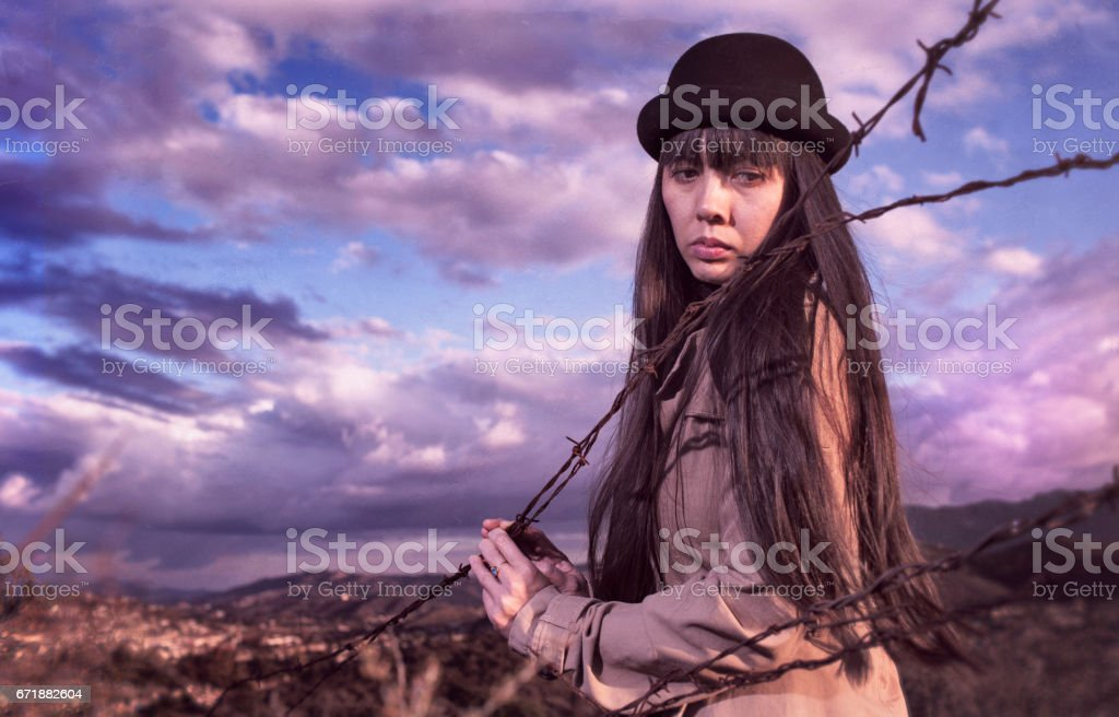 Native American Indian woman in a black hat stands at a barbwire fence at the edge of a reservation with a dramatic cloudy sky behind her stock photo