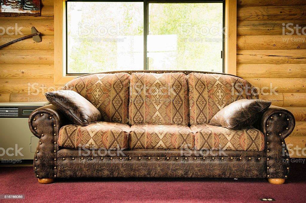 Native American Inspired Leather Sofa In Log Cabin Stock