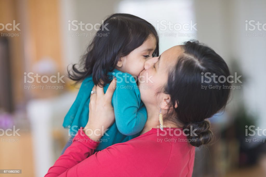 Native American mom picks up her young daughter to give her a big kiss stock photo