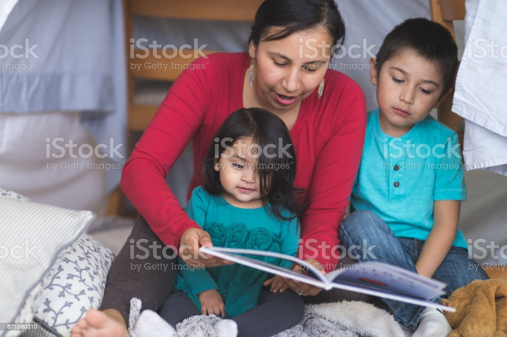 Native American mom reads with her two children under makeshift fort in living room stock photo