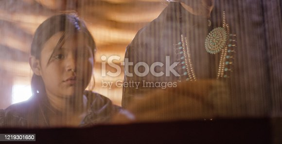 istock A Native American Teenage Girl (Navajo) Watches a Female Member of Her Family Weave on a Loom inside a Hogan (Navajo Hut) 1219301650