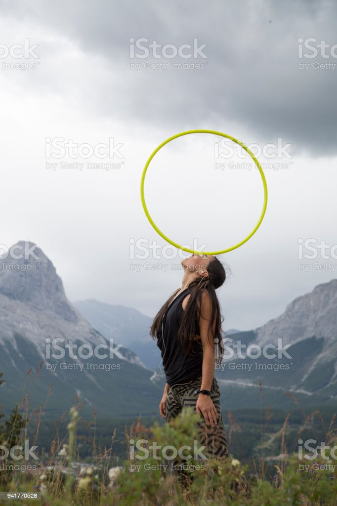 Native American woman dances with hoops, in mountains stock photo