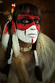 Native american woman portrait with painted face. Young beautiful woman in native american costume with wolf fur and war mask on her face