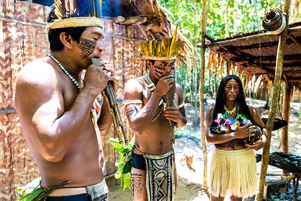 Native Brazilian group playing wooden flute stock photo