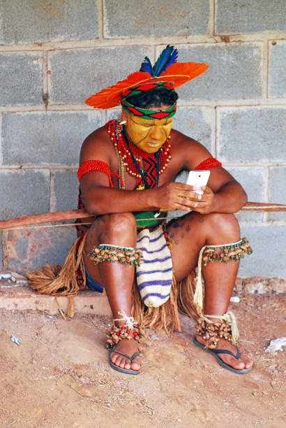 Native Brazilian man from an Indigenous tribe using a mobile phone. stock photo