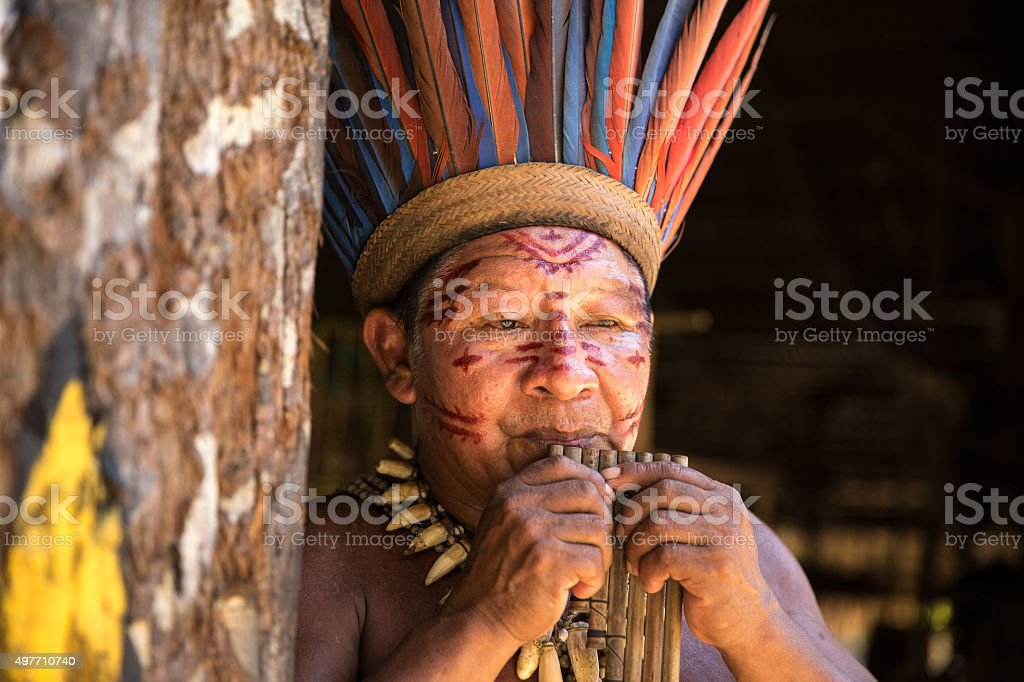 Native Brazilian old man playing wooden flute stock photo