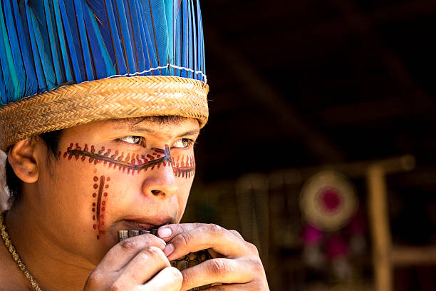 Native Brazilian playing wooden flute stock photo