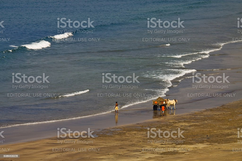Native collecting sand from beach stock photo