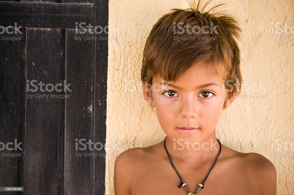 Native Mexican boy against colorful stucco wall stock photo