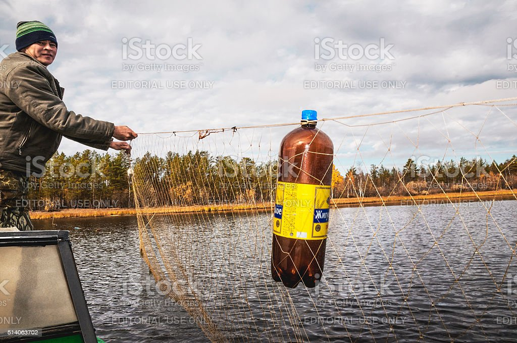 Native of the North in the boat with fishing nets. stock photo