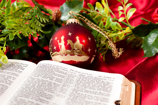 Nativity Red Christmas ornaments with open Bible.  Scripture is open to Luke and the story of the Birth of Jesus.