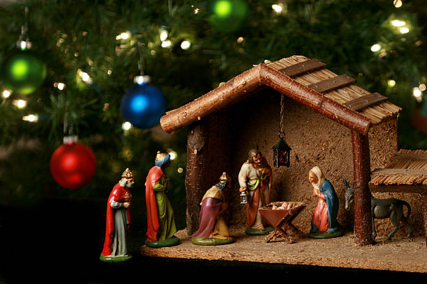 nativity scene next to a christmas tree - nativity scene stock pictures, royalty-free photos & images