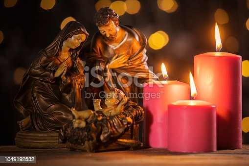 Christmas nativity scene of baby Jesus on the manger with burning candles and blurred sparkling light background